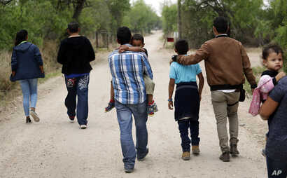 FILE - Migrant families walk from the Rio Grande, the river separating the U.S. and Mexico in Texas, near McAllen, Texas, right before being apprehended by Border Patrol, March 14, 2019.