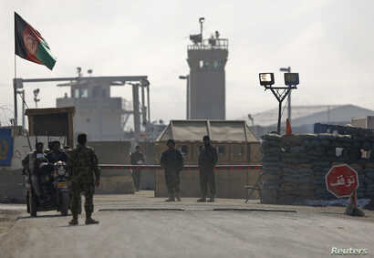 FILE - Afghan National Army (ANA) soldiers stand at the Bagram detainee centre gate north of Kabul, Feb. 13, 2014.