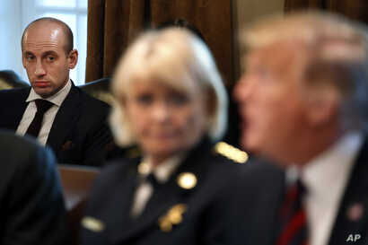 White House senior adviser Stephen Miller, left, listens listens as President Donald Trump, at right, speaks during a roundtable discussion on border security with local leaders, Jan. 11, 2019, in the Cabinet Room of the White House in Washington.