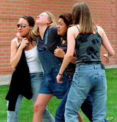 FILE -- In an April 20, 1999 file photo unidentified young women head to a library near Columbine High School where students and faculty members were evacuated after two gunmen went on a shooting rampage in the school in the southwest Denver suburb o...
