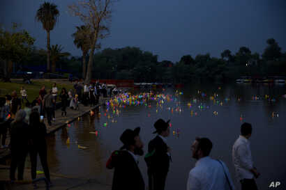 People look upon floating handmade boats with the names of Nazi concentration camps, during a ceremony marking the annual Holocaust Remembrance Day in Hayarkon park in Tel Aviv, Israel, May 1, 2019.