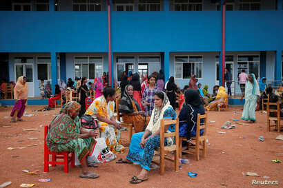 People relocated to a school buildingbecause of an overnight gunbattle between troops and suspected Islamist militants on the east coast ofSriLanka are seenin Kalmunai, April 27, 2019.