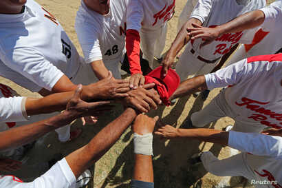 FILE - Members of Family Rose softball team put their hands together before a match at Lecuna Avenue softball pitch in Caracas, Venezuela, March 24, 2019.