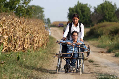 FILE - Nujeen Mustafa, refugee from Syria in a wheelchair moves toward the Croatian village of Tovarnik, close to the official Serbia-Croatia border, Sept. 16, 2015.