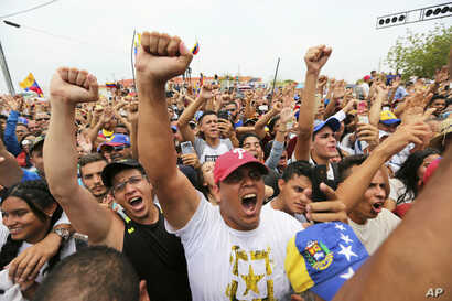Supporters of Venezuela's National Assembly President and self-proclaimed interim president of Venezuela, Juan Guaido, cheer during his rally on the shores of Maracaibo Lake in Cabimas, Venezuela, April 14, 2019.
