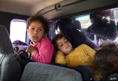 Syrian children wait to leave their home following reported regime shelling on Hama and Idlib provinces on May 1, 2019.