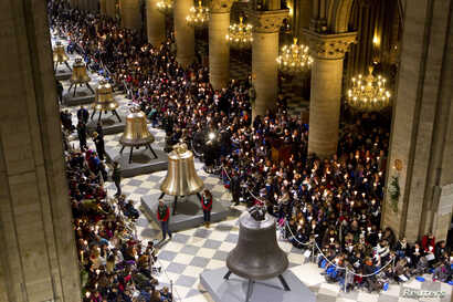People attend a ceremony to bless the new eight bronze bells of Notre-Dame de Paris Cathedral in Paris, France, Feb. 2, 2013.