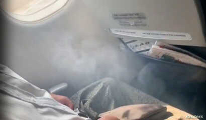 Smoke enters the cabin as passengers wait to evacuate after Myanmar National Airlines flight UB103 landed without a front wheel at Mandalay International Airport in Tada-U, Myanmar, May 12, 2019 in this image taken from social media video.