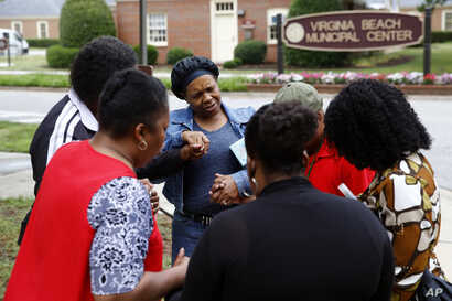 Members of Mount Olive Baptist Church pray near a municipal building that was the scene of a shooting, June 1, 2019, in Virginia Beach, Va