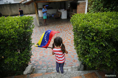 FILE - A girl waves the Venezuelan flag during a visit to bid goodbye in her grandparents' house, before her move to the U.S. after winning the green card lottery, in Valencia, April 6, 2014.