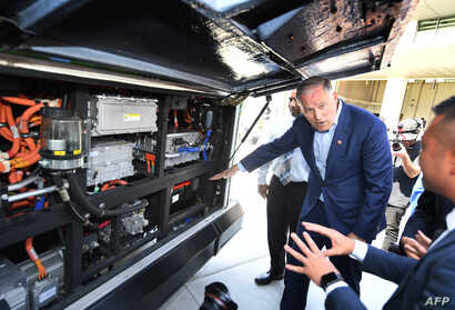 Democratic presidential hopeful Jay Inslee inspects an electric bus during a tour of the Los Angeles Department of Transportation bus depot in Los Angeles, May 3, 2019.