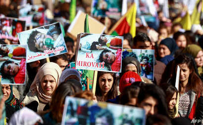 FILE - Syrian Kurds wave banners and placards during a demonstration in Qamishli, Jan. 20, 2019, marking the first anniversary of the takeover of the northern Syrian city of Afrin by the Turkish army and Turkish-backed Syrian rebels.