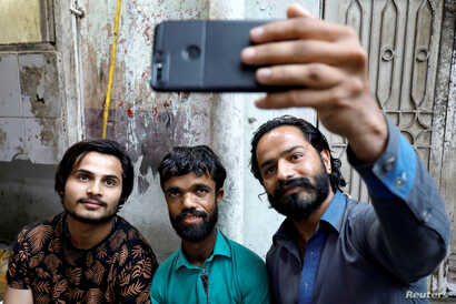 "People take selfie with Rozi Khan, 26, a waiter and a lookalike of Hollywood's actor Peter Dinklage, who plays a character of Tyrion Lannister in the TV series ""Game of Thrones,"" in Rawalpindi, Pakistan, April 28, 2019."