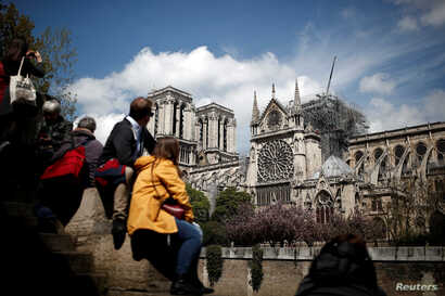 People look at Notre-Dame Cathedral two days after a massive fire devastated large parts of the gothic structure in Paris, Apr. 17, 2019.