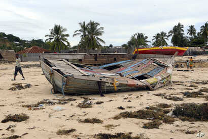 A boy walks past a fishing boat that was destroyed when Cyclone Kenneth struck in Pemba city on the northeastern coast of Mozambique, April, 27, 2019.