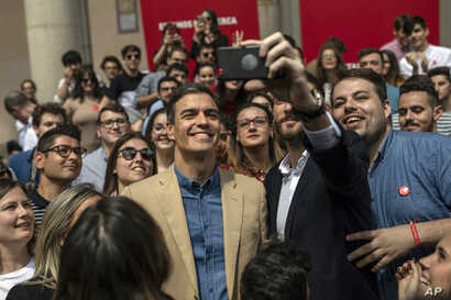 Spanish Prime Minister and Socialist Party candidate Pedro Sanchez, center, smiles for a photo during an election campaign event in Toledo, central Spain, April 26, 2019. What undecided voters do in this tight race will shape the fortunes of the two ...