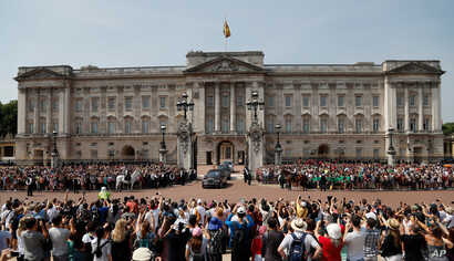 FILE - ueen Elizabeth II leaves Buckingham Palace with Prince Charles to travel to parliament for her speech at the official State Opening of Parliament in London.