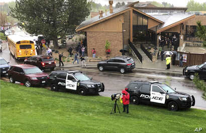 Police and others are seen outside STEM School Highlands Ranch, a charter middle school in the Denver suburb of Highlands Ranch, Colo., after a shooting May 7, 2019.