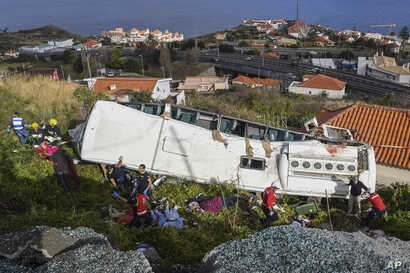 Rescue officials attend the scene after a tour bus crashed in Canico on Portugal's Madeira Island, April 17, 2019.