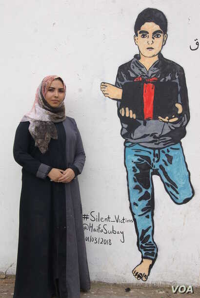 Yemeni artist Haifa Subay stands in front of one of her murals in the Yemeni capital, Sanaa. The mural shows a boy holding a leg he lost in a land mine explosion — one of the issues Subay wants to shed light on. Land mines in Yemen have killed almo...