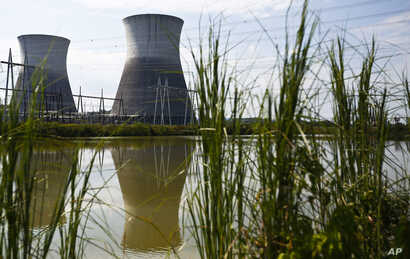 FILEL - Two cooling towers can be seen in the reflection of a pond outside of the unfinished Bellefonte Nuclear Plant, in Hollywood, Alabama, Sept. 7, 2016.