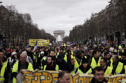 FILE - Yellow Vests protesters march on the Champs Elysees avenue in Paris. France's yellow vest protesters remain a force to be reckoned with five months after their movement started, and as President Emmanuel Macron announces his responses to their...