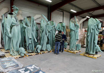 Consultant Patrick Palem (R) checks statues that were removed from the spire of Paris' Notre-Dame Cathedral in a workshop at the Socra company for restoration work in Marsac-sur-L'Isle, France, April 16, 2019.