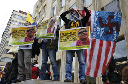 FILE - Supporters of Seuxis Paucias Hernandez, better known by his alias Jesus Santrich, a leader of the former Revolutionary Armed Forces of Colombia (FARC), hold posters asking for his freedom during a demonstration marking May Day to honor workers...