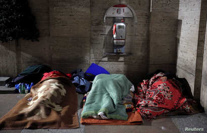 Homeless people sleep in passageway near St. Peter's square in Rome, Italy, Jan. 11, 2017.