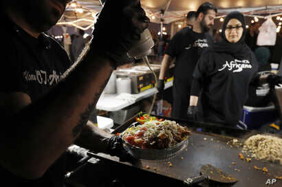 Ali el Romh of Peepo's Subs and Shawarma creates a chicken platter at the Ramadan Suhoor Festival in Dearborn Heights, Mich.