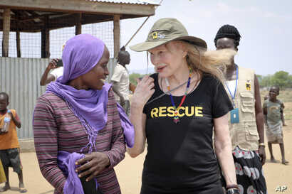 FILE - Human rights activist Mia Farrow talks with staff from the International Rescue Committee while visiting an internally displaced persons camp in Juba, South Sudan. As envoy for the International Rescue Committee, she is helping the aid group p...