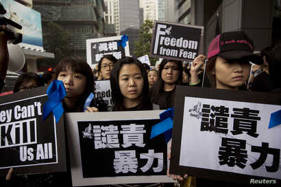 FILE - Staff members of Ming Pao newspaper take part in the march against violence on journalists in Hong Kong March 2, 2014.