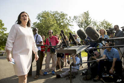 White House press secretary Sarah Huckabee Sanders takes a question from a reporter on the North Lawn outside the West Wing at the White House in Washington.