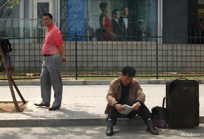 FILE - People waiting to apply for visas sit outside the U.S. embassy in Beijing, China, May 3, 2011.