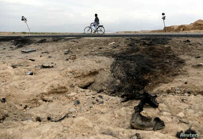 FILE - An Afghan man rides on a bicycle past the site of a car bomb attack where U.S soldiers were killed near Bagram air base, Afghanistan, April 9, 2019.