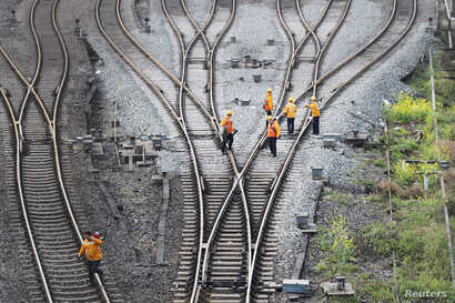 FILE - Workers inspect railway tracks for the Belt and Road freight rail route linking Chongqing, China, with Duisburg, Germany, at the Dazhou railway station in Sichuan province, China March 14, 2019.