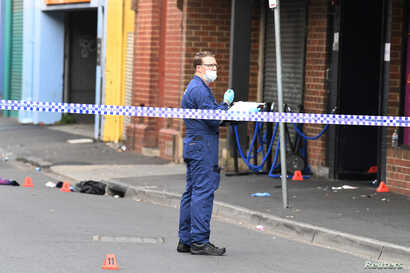 A Victoria Police employee works at the scene of a multiple shooting outside Love Machine nightclub in Prahran, Melbourne, Australia, April 14, 2019.