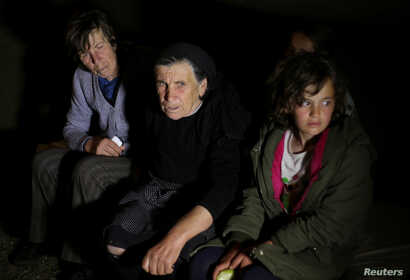 Evacuated residents sit inside a tent at a temporary shelter erected after an earthquake in Floq, Albania, June 1, 2019.