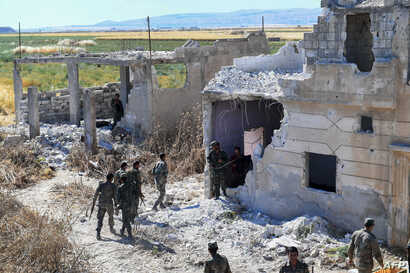 Syrian regime forces gather near a damaged building at the entrance of the town Kafr Nabuda, in the north of the Syrian Hama province, May 26, 2019.