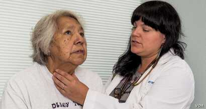 In this photo, an unidentified Indian Health Service physician checks a patient's thyroid. Native Americans suffer a higher mortality rate from cancer than other population groups.  Early screening, say experts, is key to survival. Courtesy:  HHS-IHS...