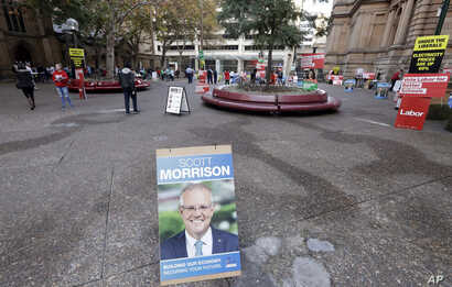 A placard with the face of Australian Prime Minister Scott Morrison is placed near the entrance of Town Hall as voters line up to cast their ballots in a federal election Sydney, Australia, May 18, 2019.