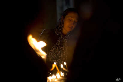 A Christian woman prays in the Church of the Holy Sepulchre, traditionally believed by many to be the site of the crucifixion of Jesus Christ, during the Holy Week procession in Jerusalem's old city, April 20, 2019.