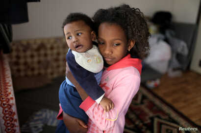 A displaced Libyan girl, who fled her house because of the fighting between the Eastern forces commanded by Khalifa Haftar and the internationally recognized government, carries her son at the industrial complex, which is used as a shelter, in Tripol...