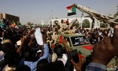 Sudanese soldiers are seen on their vehicles as they move with a military convoy outside the defense ministry compound in Khartoum, Sudan, April 25, 2019.