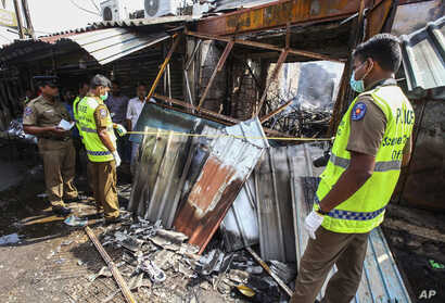Sri Lankan security officers inspect vandalized shops owned by Muslims in Minuwangoda, a suburb of Colombo, May 14, 2019.