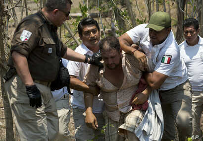 A Central American migrant is detained by Mexican immigration agents on the highway to Pijijiapan, Mexico, Apr. 22, 2019.
