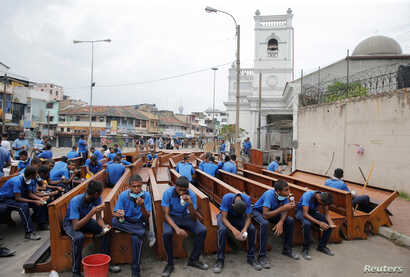 Workers sit on pews as they take a break from repairs outside St. Anthony's Shrine a week after a string of suicide bomb attacks across the island on Easter, in Colombo, Sri Lanka, April 28, 2019.