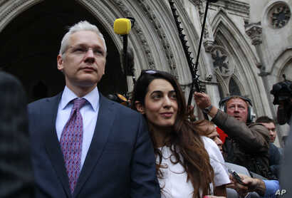 FILE - Wikileaks founder Julian Assange, left,  leaves Britain's Royal Courts of Justice after his extradition appeal was heard in central London, July 13, 2011.