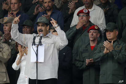 FILE - In this April 13, 2019 file photo, Venezuela's President Nicolas Maduro, speaks flanked by Defense Minister Vladimir Padrino Lopez, right, and Gen. Ivan Hernandez, second from right, head of both the presidential guard and military counterinte...
