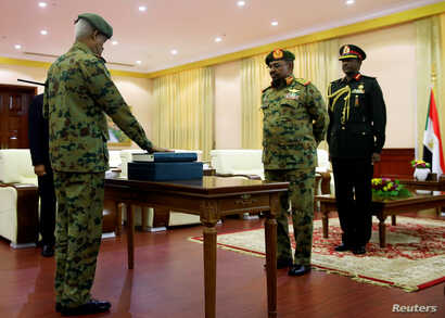 FILE - Defense Minister Awad Mohamed Ahmed Ibn Auf (L), a former military intelligence chief, is sworn in as first vice president in front of Sudan's President Omar al-Bashir during a swearing in ceremony of new officials after Bashir dissolved the c...